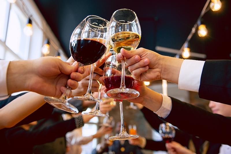 Kollegaer fester og skåler i rødvin og hvidvin til personalefest.