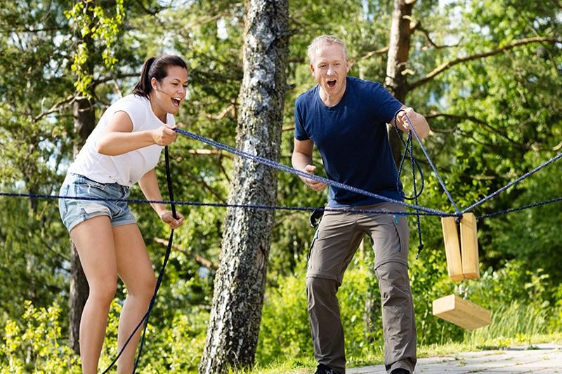 To kollegaer samlet om sjov aktivitet i skoven.