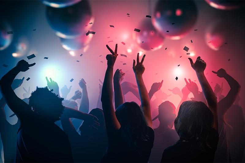 Kollegaer danser og fester sammen til personalefest med armene i vejret.